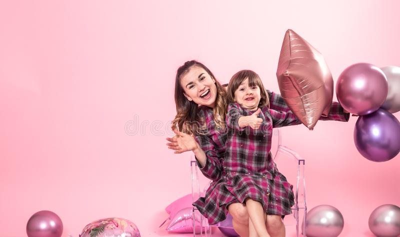 Funny mom and child sitting on a transparent stylish chairs pink background. Little girl and mother having fun with balloons and. Confetti. The concept of royalty free stock photo