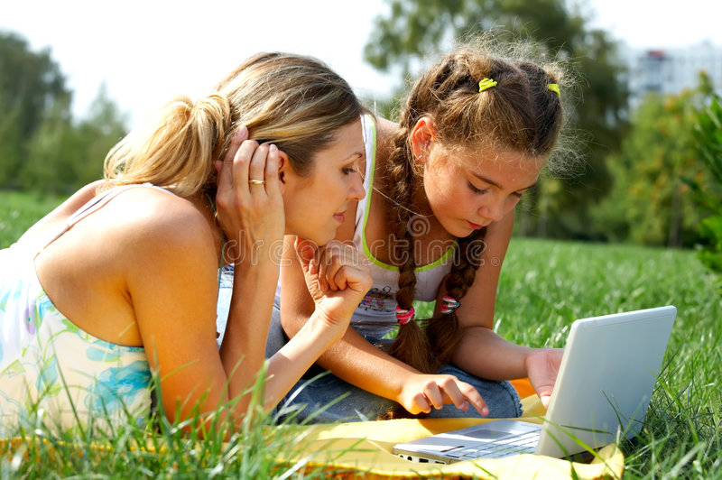 Funny mom and daughter with laptop stock photography