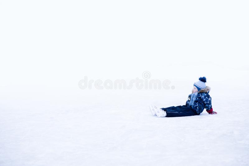 Funny moment - cute little boy fell on the ice skating rink.  stock photography