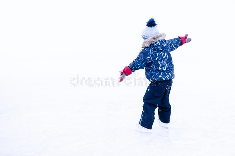 Funny moment - cute little boy fell on the ice skating rink.  royalty free stock photos