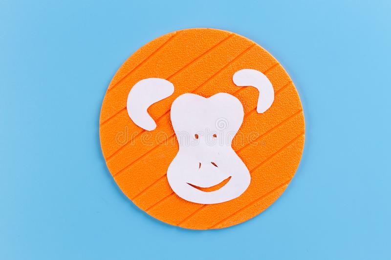 Funny monkey made of paper. Blue background stock images