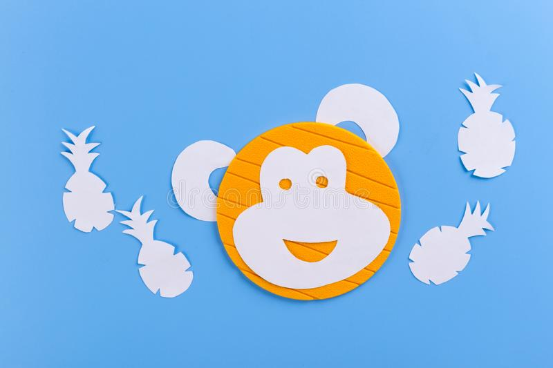 Funny monkey made of paper. Blue background stock photos
