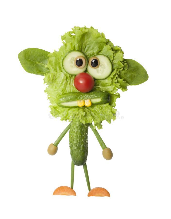 Funny monster made with fresh green vegetables. Funny monster made with salad, cucumber and carrot. Creative idea to make a fantasy creature with simple food stock photos