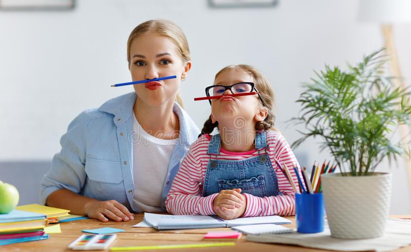 Funny mother and child daughter doing homework writing and reading. At home stock photos