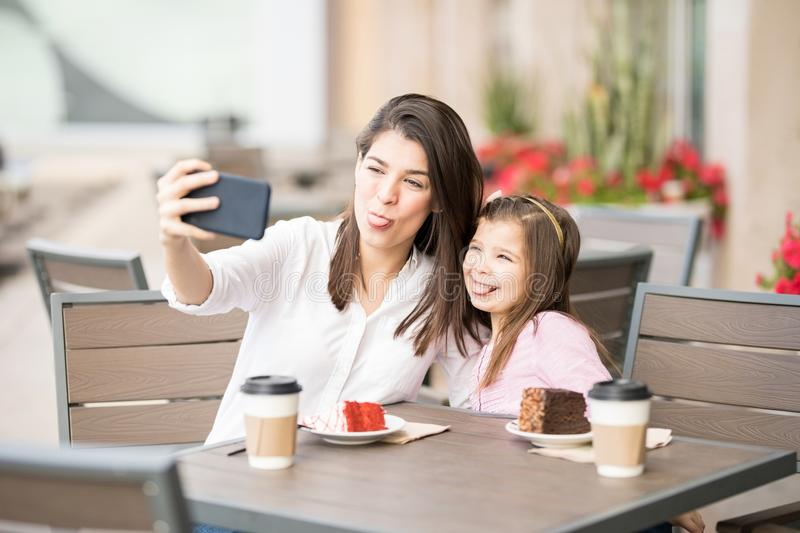 Funny mother and daughter taking selfie at cafe royalty free stock image
