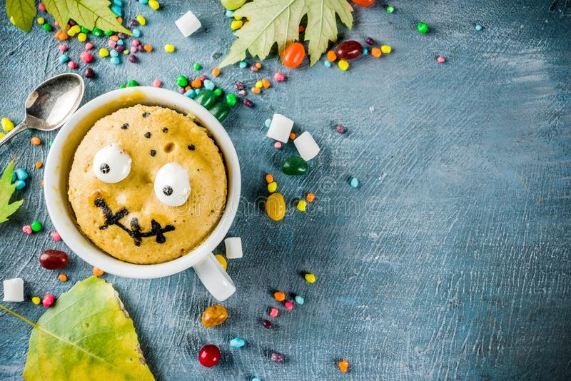 Funny mug cake for Halloween. Kids Halloween food idea, funny mug cake decorate like monster face with marshmallow eyes and mouth painted with edible marker stock photography