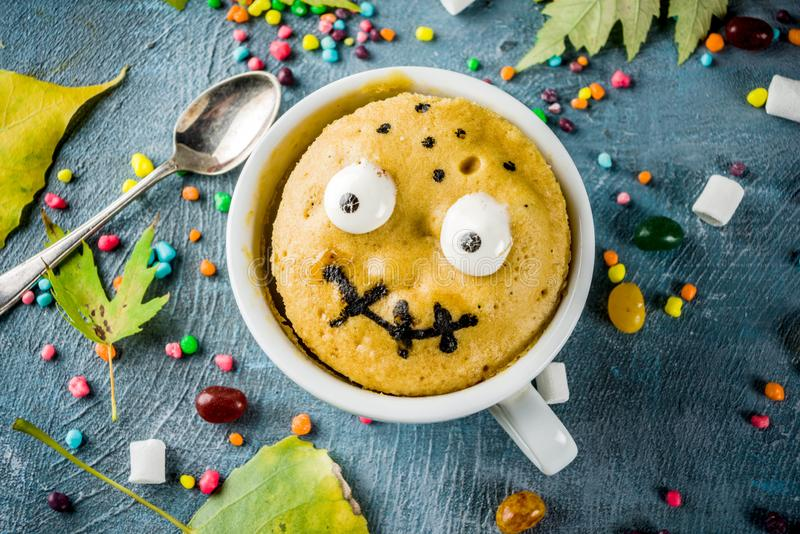 Funny mug cake for Halloween. Kids Halloween food idea, funny mug cake decorate like monster face with marshmallow eyes and mouth painted with edible marker stock images