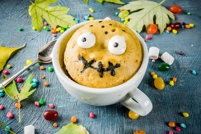 Funny mug cake for Halloween. Kids Halloween food idea, funny mug cake decorate like monster face with marshmallow eyes and mouth painted with edible marker stock photos