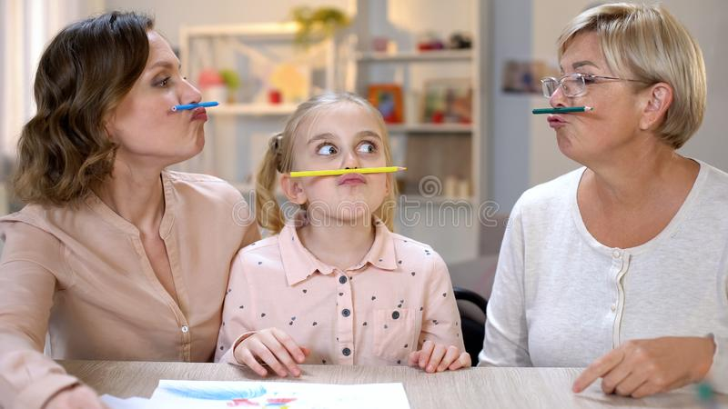 Funny multi-generation females holding color pencils between nose and lips, game stock photo