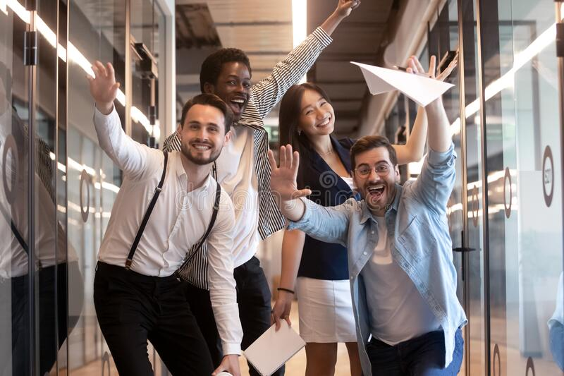 Funny multiethnic employees posing for picture in office hallway stock photos