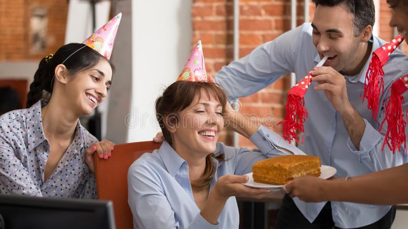Excited diverse workers congratulate colleague with birthday in office stock image