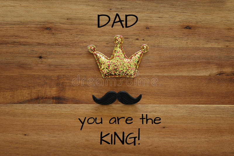 Funny mustache and glitter crown. Father& x27;s day concept. Top view image of funny mustache and glitter crown on wooden background. Father& x27;s day concept stock image