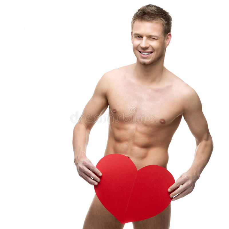 Funny naked man holding big red paper heart. Young cheerful caucasian funny naked man holding big red paper heart isolated on white background with falling red stock photo