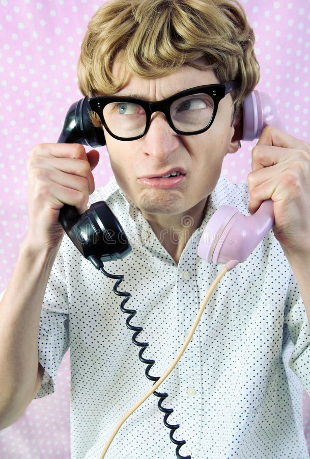 Funny nerd. Busy having a conversation on two phones stock photo