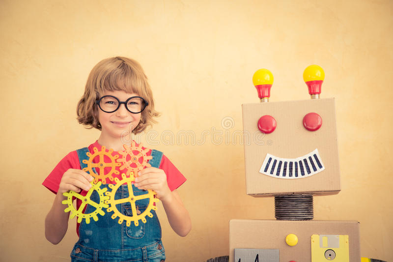 Funny nerd child with toy robot. Innovation technology and success concept royalty free stock images
