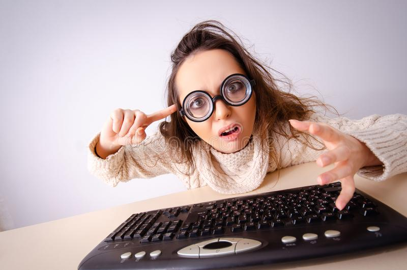 Funny nerd girl working on computer. The funny nerd girl working on computer stock image