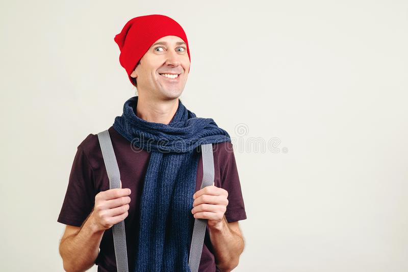 Funny nerd guy pulling his suspenders. Trendy hipster in hat and scarf on grey wall, with copy space. Young man with new idea royalty free stock image