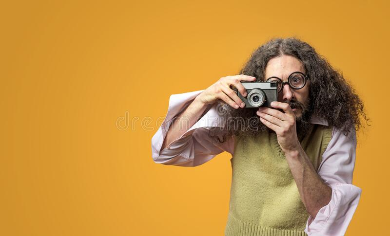 Funny nerd taking a picture with a digital camera stock photography