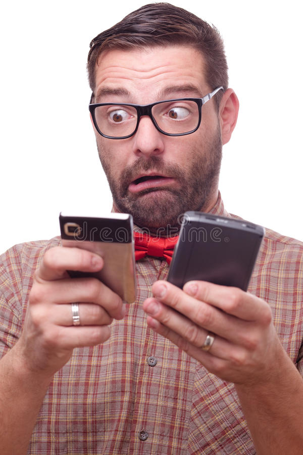Funny Nerd Torn Between Two Gadgets Royalty Free Stock Images