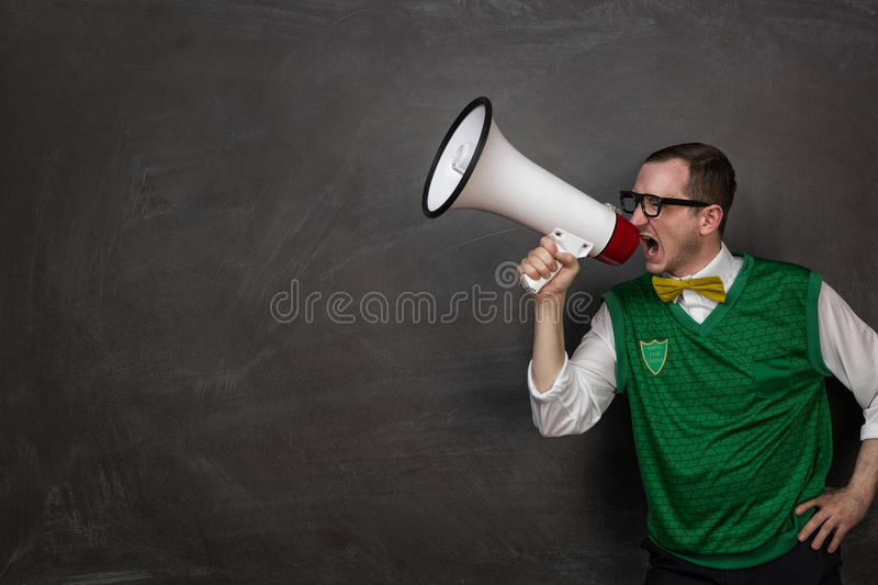 Funny nerd yelling at the megaphone. Funny retro nerd yelling through the megaphone with copy space royalty free stock photography
