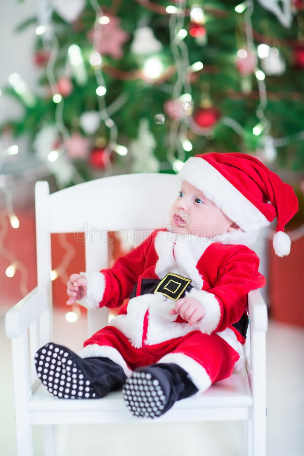 Funny newborn baby boy in Santa outfit under under Christmas tree royalty free stock photos