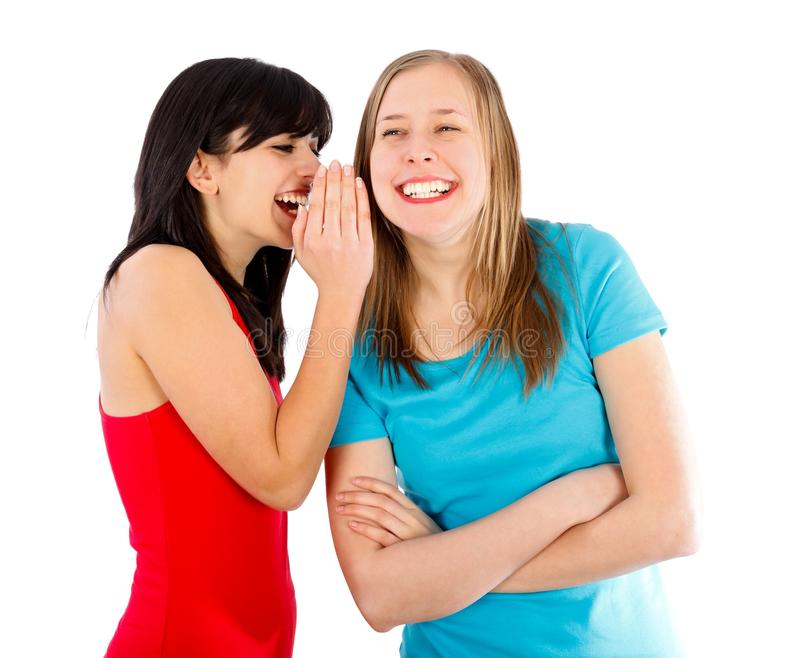 Funny news. Brunette whispering something funny to her blond friend stock images