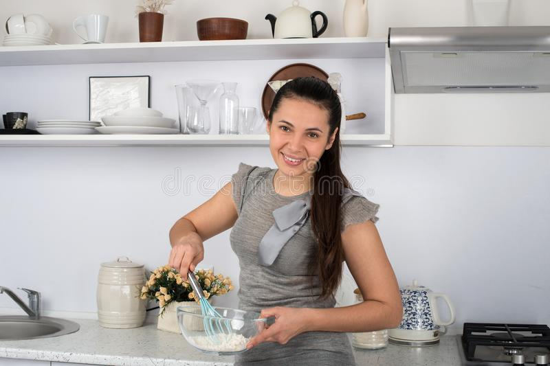 The funny beautiful housewife in kitchen prepares. stock image