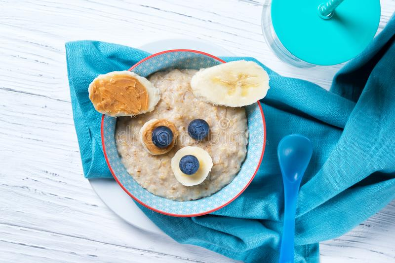 Funny oat porridge with dog, puppy face made of fruit, berries and peanut butter, food for kids idea, top view royalty free stock photography
