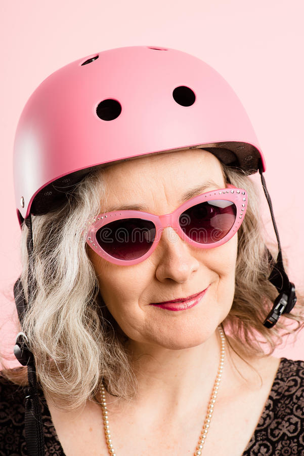 Funny woman wearing Cycling Helmet portrait pink background real. Funny old aged woman wearing cycling helmet royalty free stock photos