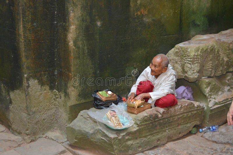 Funny old man seated in angkor wat temple, stock image