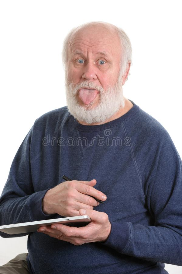 Funny old man with tongue sticking out using tablet computer isolated on white. Funny bald and bearded senior man with tongue sticking out using tablet computer stock photo