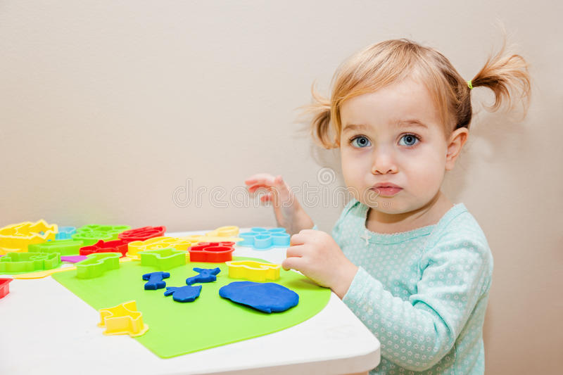 Funny one year old girl playing with colorful dough at home or daycare. royalty free stock photo