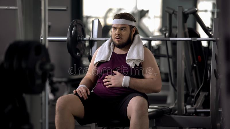 Funny overweight male stroking belly, exhausted after workout, insecurities stock photo