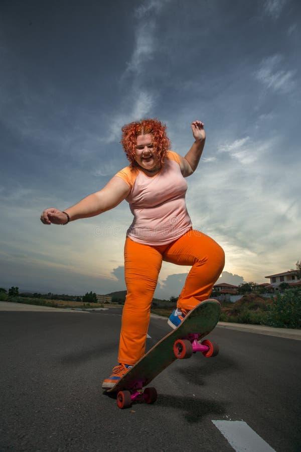 Skateboarding fat woman on skateboard royalty free stock images