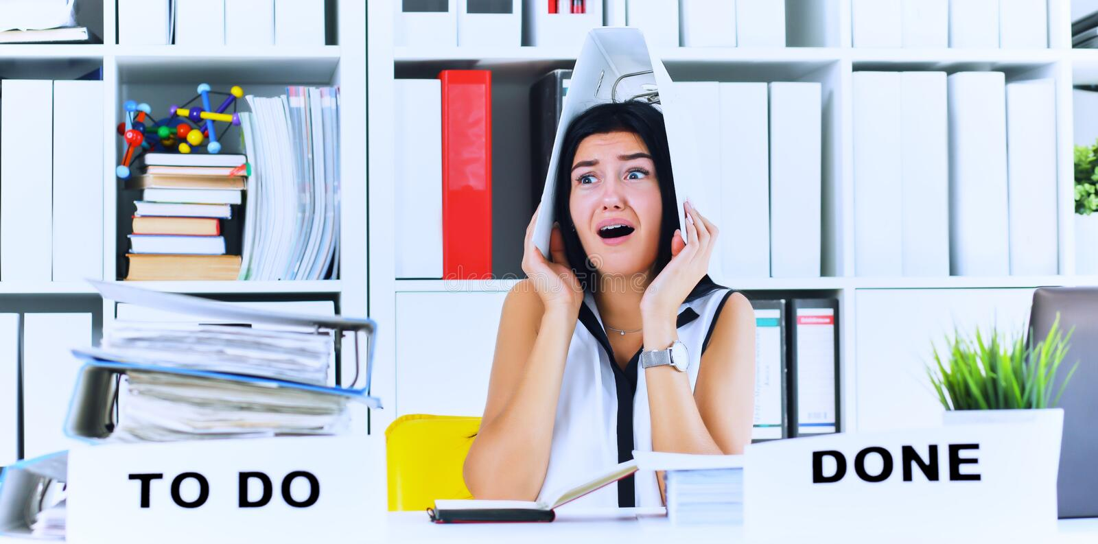 Funny overworked girl with a folder on her head sitting in the workplace cluttered with folders. Reaction of a. Subordinate when the boss orders her to do too stock photography