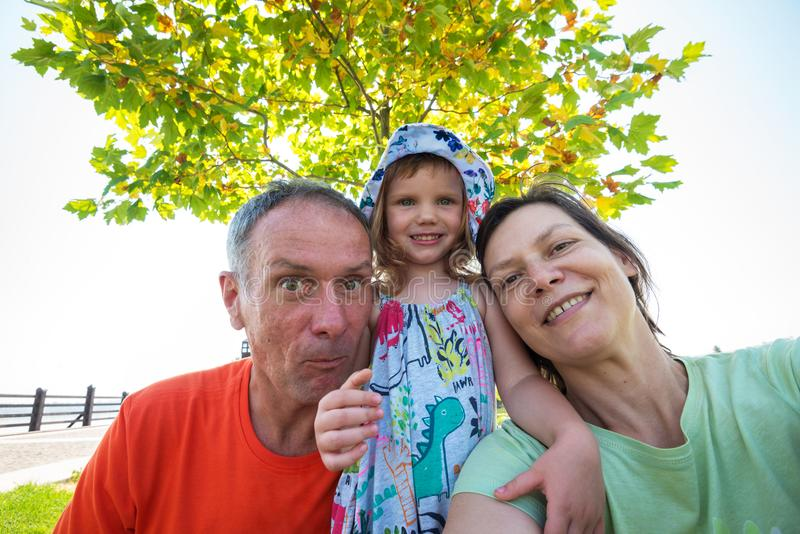 Funny parents with small laughing daughter taking selfie in the royalty free stock images