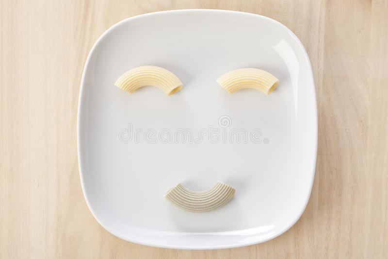 Funny pasta pace. Funny pasta face with italian raw handmade pasta on a white dish royalty free stock photography