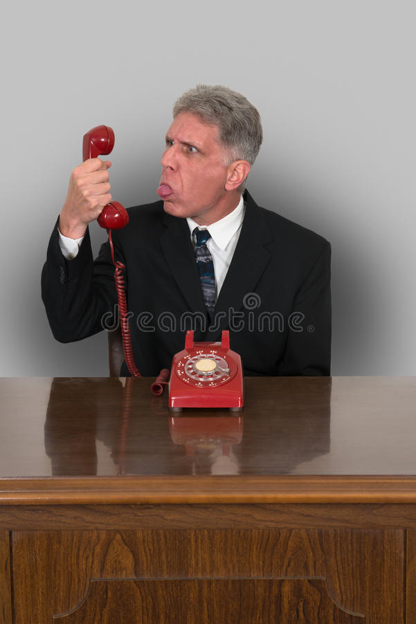 Funny Phone Sales, Business, Marketing. A funny businessman is mean and angry while working at his desk while trying to do phone sales, marketing, or regular royalty free stock photo