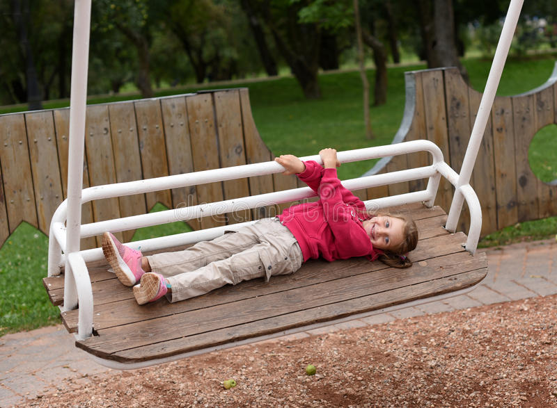 A little girl swinging on a swing in a park royalty free stock photo