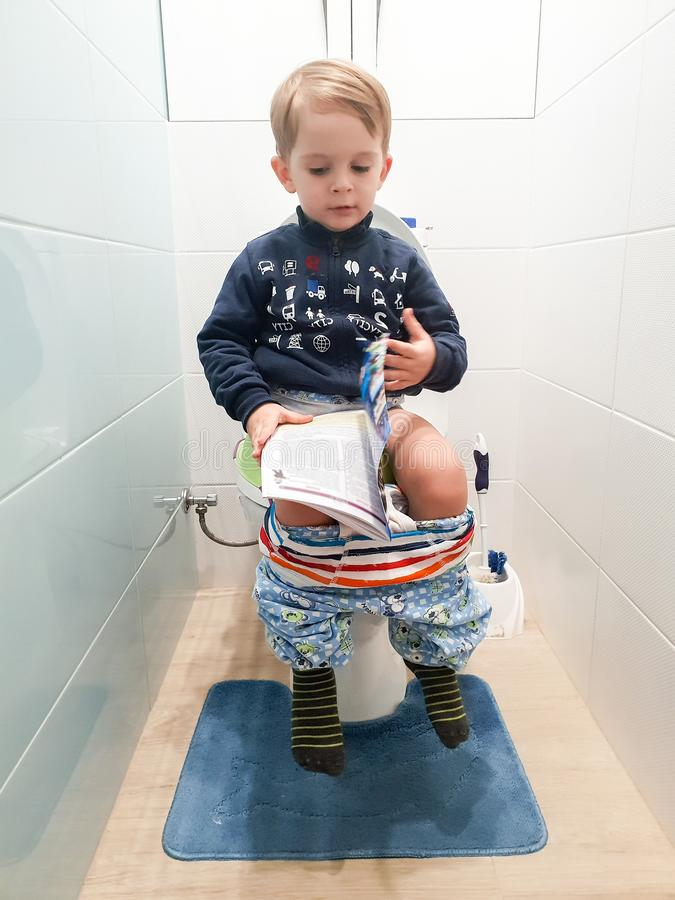 Funny image of little 3 years old toddler boy sitting on the toilet and reading magazine stock image