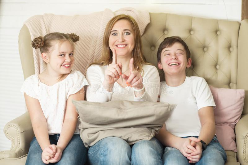 Funny photo session of a mother with two children sitting on the couch stock images