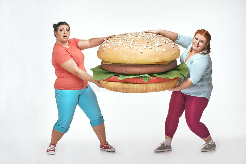 Two chubby women are holding a huge sandwich stock photos