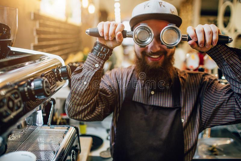 Funny picture of bearded barista in apron holding tow cezve and cover eyes with them. He smiles a bit. Guy stand at royalty free stock photography