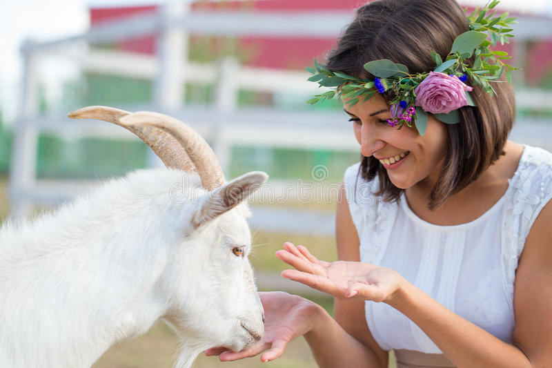 Funny picture a beautiful young girl farmer with a wreath on her royalty free stock photography
