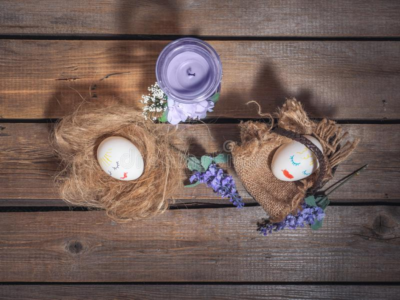Funny picture for Easter. Eggs with painted faces. Basket and straw, next are sprigs of flowers on a wooden background stock image