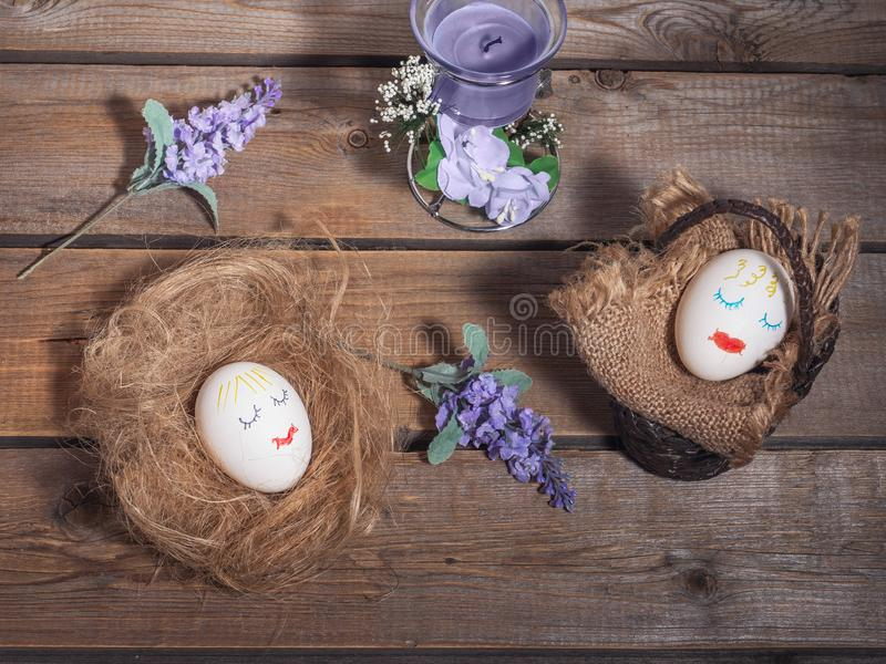 A funny picture for Easter, two eggs with painted faces. Basket and straw on which eggs sleep. stock images