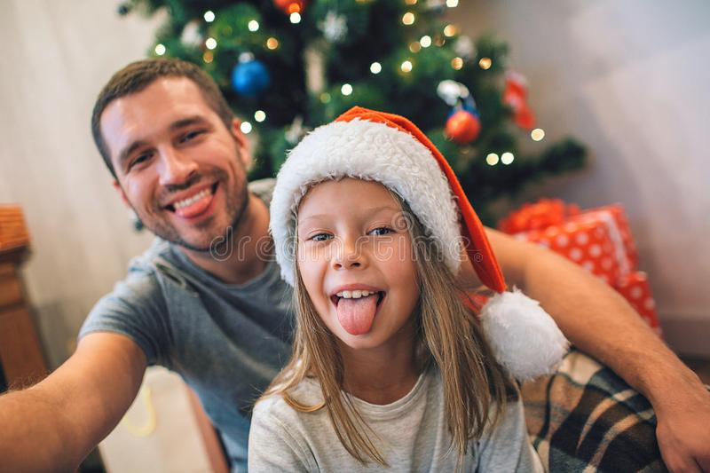 Funny picture of father and daughter showing tongues on camera. They are playing and having fun. There are Christmas stock image