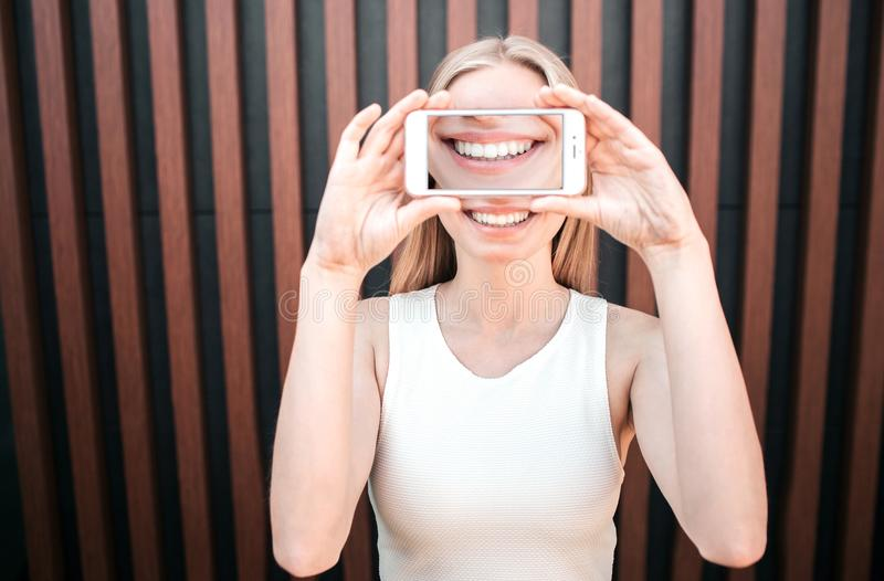 Funny picture of girl covering her face with a phone where is a picture of smile. Girl is smiling as well. Isolated on royalty free stock images