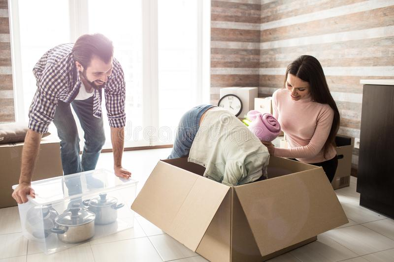 Funny picture of girl that is trying to find something in the box. Her parent are working besides her and laughing from royalty free stock images