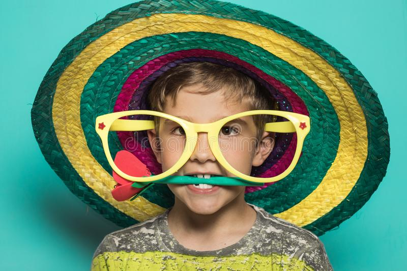 Funny picture of a kid with a props. Kid with a Mexican hat. royalty free stock image
